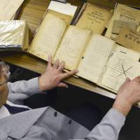 Wakayama University professor Haruo Erikawa last Oct. 27 compares an English textbook from World War II (left) with one immediately after the war to analyze revisions enforced by the government. The alterations, including changes of words and blackening out or removal of undesirable entries, reflect the values and ideologies the authorities of the time wanted to instill in Japanese students through language study. | KYODO