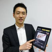 Masanari Matsuda, president of Hachimenroppi, a Tokyo-based wholesaler of fresh fish, displays a tablet with an ordering app the company developed. | KYODO