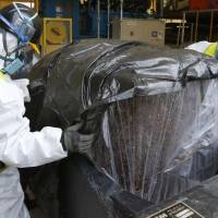 Workers wearing protective gear put compressed radioactive waste into a protective storage bag in March 2013 at a temporary storage site in Naraha, Fukushima Prefecture, inside the restricted zone near the Fukushima No. 1 nuclear power plant. | AP