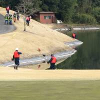 Police conduct an investigation Wednesday at a pond in the Nagoya Hills Golf Club in Kani, Gifu Prefecture, where two 8-year-old boys drowned the previous evening.   KYODO
