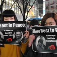 Sisters Shiori (left) and Nanami Katori mourn Kenji Goto and Haruna Yukawa, the two Japanese hostages killed by the Islamic State group, during an event at Hachiko square in Tokyo's Shibuya Ward on Sunday. | YOSHIAKI MIURA