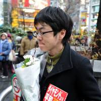 A 30-year-old company worker, who asked not to be identified, holds a bouquet and a copy of Kenji Goto's book 'Daiyamondo Yori Heiwa ga Hoshii' ('We Want Peace, Not Diamonds'), the story of a child soldier in Sierra Leone, during a mourning event for him journalist and fellow slain hostage Haruna Yukawa at Hachiko square in Tokyo's Shibuya district on Sunday. | YOSHIAKI MIURA