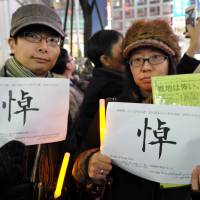 Kanako Takahashi (right), a Tokyo company employee and a friend of Kenji Goto, joined Sunday's event in Shibuya's Hachiko square with a friend. 'I'm sad, and I'm full of regret. What do we do without him?' she said. The Chinese character on their placards means 'mourning'; underneath is a quote from Goto. | YOSHIAKI MIURA