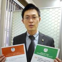 Lawyer Shiki Tomimasu hopes the leaflets, seen here in December, will help Korean students trust society. | KYODO