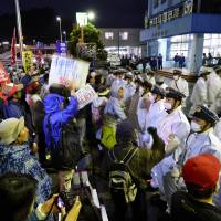 People gather in front of Nago Police Station in Okinawa Prefecture on Sunday to call for the release of two protesters arrested for allegedly trespassing at the gate of Camp Schwab. | KYODO