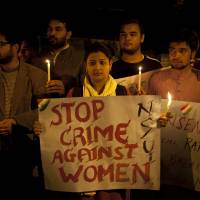 Indian youth hold candles during a protest over sexual violence in New Delhi on Monday, when police launched a search for a man who raped a Japanese student sightseeing in northern India. Elsewhere they announced the arrest of eight men suspected of brutally raping and killing a Nepalese woman, as India authorities continue to struggle to address chronic sexual violence. | AP