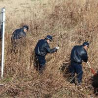 Investigators comb a bank of the Tama River in Kawasaki on Saturday for clues that may be related to the murder of 13-year-old Ryota Uemura, whose body was discovered nearby early Friday morning. KYODO