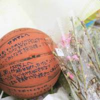 A basketball bearing messages for slain Ryota Uemura, 13, lies with flowers Tuesday on a bank of the Tama River in Kawasaki.  | KYODO