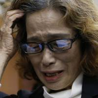 Junko Ishido, mother of slain journalist Kenji Goto, who was held captive by Islamic State militants, touches her head as she speaks to reporters at her Tokyo home Sunday. Islamic State militants said earlier they had beheaded Goto, the second Japanese hostage, after the failure of international efforts to secure his release through a prisoner swap. | REUTERS