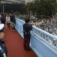 A policeman on a pedestrian overpass guards the Tokyo Marathon Sunday. The Tokyo race was held amid tightened security, following the slaying of two Japanese hostages by the Islamic State group last month. Islamist militants threatened Japanese people everywhere after the slayings. | AP