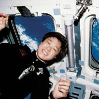 Astronaut Chiaki Mukai poses for a photo aboard the space shuttle Discovery during her second space mission in 1998. | NASA/JAXA/KYODO