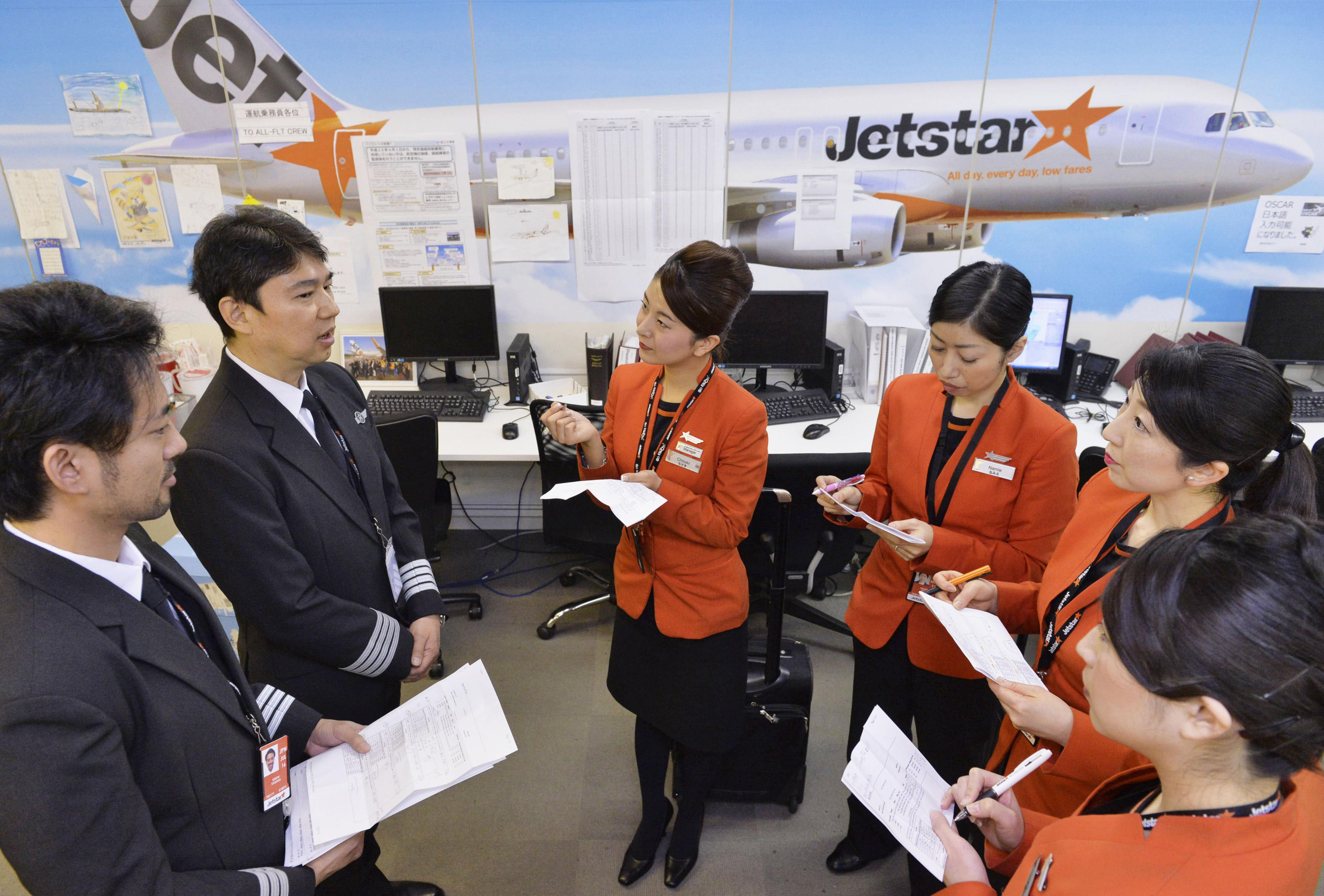 Pilots for Jetstar Japan brief the cabin staff before departing from Narita International Airport on Jan. 22. LCCs are facing an acute pilot shortage that is crimping their expansion plans. | KYODO