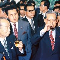 Prime Minister Eisaku Sato (right) and Foreign Minister Takeo Fukuda enjoy a tipple during a party at the prime minister's office in Tokyo in June 1976. Japan and the United States negotiated the date of Okinawa's reversion to encourage a smooth transition of power from Sato to Fukuda. | KYODO