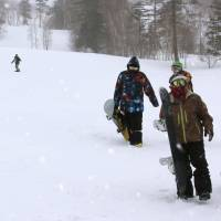 Snowboarders hit the slopes at the Ontake 2240 ski resort in Nagano Prefecture on Thursday. The resort opened two months late after officials shrank the exclusion zone set up around the volcano's vents following a surprise eruption last year. | KYODO