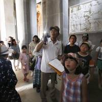 Children listen to a guide explain exhibits inside Peace Tower in Heiwadai Park in Miyazaki last Aug. 15, the 69th anniversary of the Japan's surrender in World War II. | KYODO