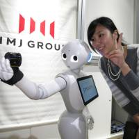 A member of Tokyo-based software team IMJ Corp. takes a photo with humanoid robot Pepper, developed by telecom company SoftBank Corp., during a application software contest for the robot held in Tokyo on Sunday. | KAZUAKI NAGATA