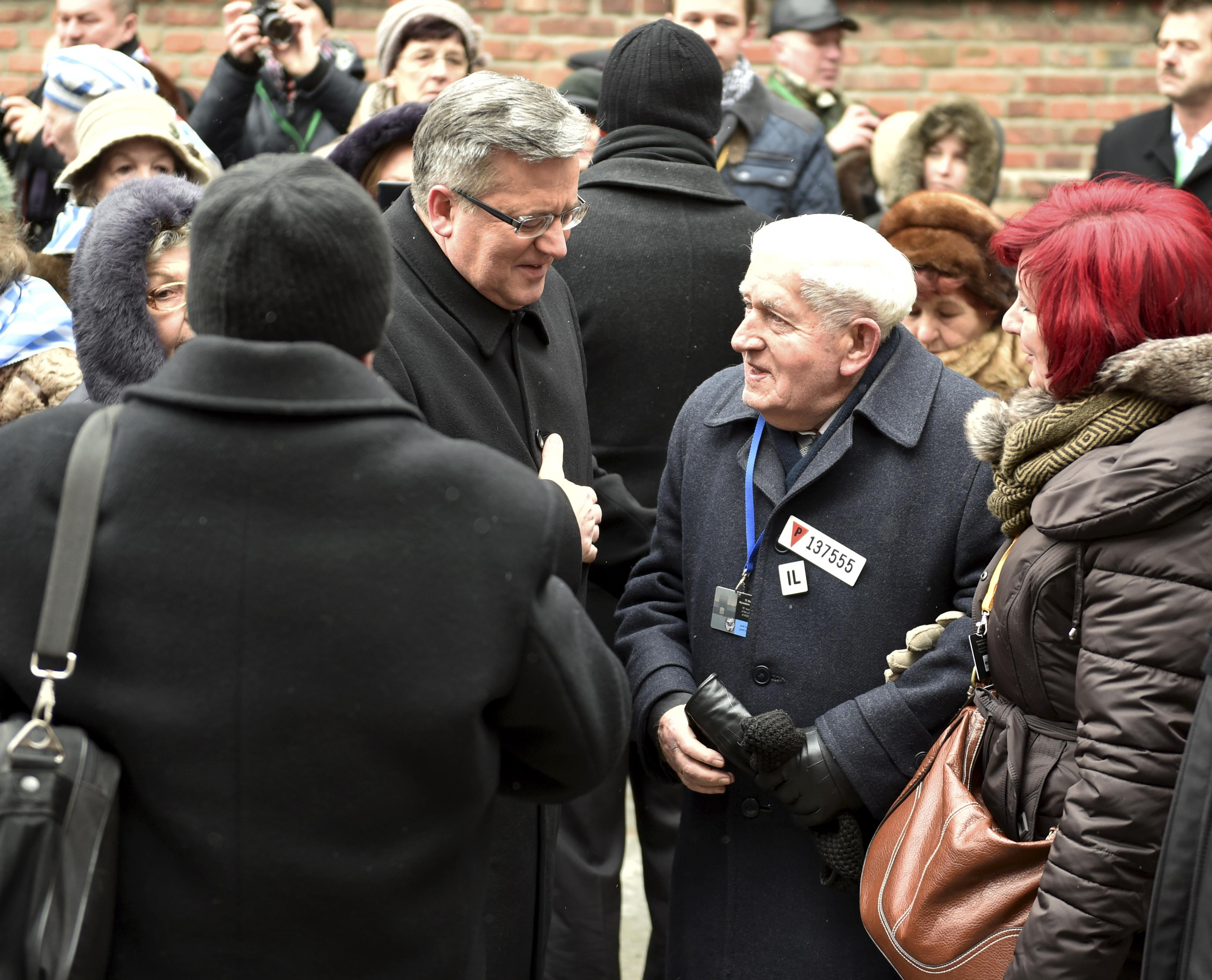 Polish President Bronislaw Komorowski (left) and survivors of the Auschwitz-Birkenau concentration camp gather at the Wall of Death on Jan. 27, the 70th anniversary of the liberation of the Nazi extermination camp in Auschwitz, Poland. The Japanese and Polish governments are arranging a summit meeting in Tokyo in late February, diplomatic sources said Saturday.   KYODO/GETTY IMAGES
