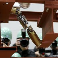 Photographers take pictures of a remote-controlled robot resembling an enlarged fiberscope as it crawls into a mock-up of a primary containment chamber during a demonstration for the media at a government facility in Hitachi, Ibaraki Prefecture, on Thursday. | AP