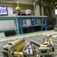 An operator controls a snake-like robotic device during a demonstration for the media at a government facility in Hitachi, Ibaraki Prefecture, on Thursday. The robot, developed by electronics giant Hitachi and its nuclear affiliate, Hitachi-GE Nuclear Energy, will examine damage inside the No. 1 reactor at the badly damaged Fukushima No. 1 nuclear power plant in April. | AP