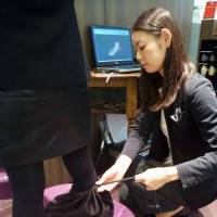 A Kibera Ginza Core salesperson takes a measurement from a customer's foot. | KYODO