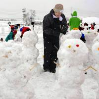 People in Iiyama, Nagano Prefecture, take part in attempt on Sunday to break the Guinness World Record for most snowmen made in one hour. The group of 630 people was successful in creating 1,583 snowmen within the time limit. | KYODO