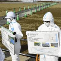 Workers discuss planned interim facilities for contaminated soil in Futaba, Fukushima Prefecture, on Tuesday. | KYODO