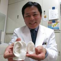 Tsuyoshi Takato, a professor of tissue engineering at the University of Tokyo School of Medicine, shows ear models. The one on the right was printed with polylactic acid, while the other was made with silicone in a mold. | KAZUAKI NAGATA