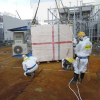This handout picture taken by Tokyo Electric Power Co. on Monday shows a measuring device of cosmic rays, to be used to look inside crippled reactors, being installed at Tepco's Fukushima No. 1 nuclear plant at Okuma, Fukushima Prefecture. The device will use muons to check fuel debris inside the reactors. | AFP-JIJI/TEPCO