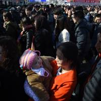 A young woman holds a baby as they wait to enter a Beijing railway station Tuesday. Hundreds of millions of Chinese are returning to their hometowns to celebrate the Lunar New Year with families in what is the world's largest annual migration. | AFP-JIJI