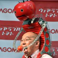Shigenori Suzuki, an employee with food-maker Kagome, tries to eat a tomato provided from the new tomato dispenser for marathon runners, dubbed Tomachan, during a demonstration on Thursday in Tokyo ahead of this weekend's Tokyo marathon. | AFP-JIJI
