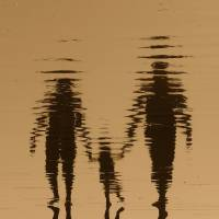 Water reflects the silhouettes of a young couple with a toddler. At least 10,000 people in Japan are thought to be unlisted on family registers and thus are considered ineligible for services such as welfare and health insurance. | ISTOCK