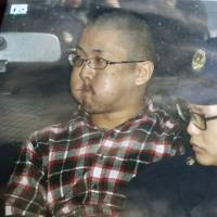 Oshu Nakamura, suspected of fatally stabbing an 11-year-old boy, is taken from a police station in Iwade, Wakayama Prefecture, to be sent to prosecutors on Sunday. Nakamura, 22, has denied killing or even knowing the victim, Toshi Morita. | KYODO