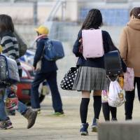Parents in Kinokawa, Wakayama Pref., escort their children home Friday, the day after an 11-year-old was stabbed to death in the area.  | KYODO