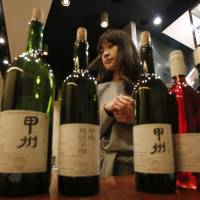 Ayana Misawa, of Grace Wine in Yamanashi Prefecture, presents some of her Koshu wine at a restaurant in Tokyo on Jan. 17. Misawa represents a generation of winemakers who believe Koshu could gain global recognition and become an important national export. | REUTERS