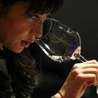 Ayana Misawa, chief winemaker of Grace Wine, smells a wine's bouquet at a restaurant in Tokyo January 17. | REUTERS