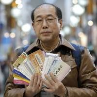 Private investor Hiroto Kiritani displays complimentary tickets for stockholders as he poses in a Tokyo shopping arcade Feb. 3. | BLOOMBERG