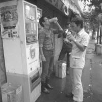 Street bar: Machines sell beer and men consume it in Tokyo in 1977. Vending machines that dispense beer can still be found in Japan, but many disappeared after a 'voluntary ban' on alcohol sales from vending machines was urged in 2000. | KYODO
