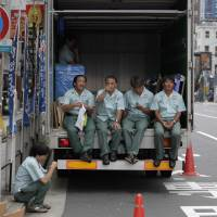 Back on truck: Workers in Tokyo exercise their legally protected right to take a breather. | AP