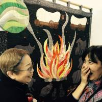In stitches: Quilters Yoshiko Katagiri (left) and Akemi Narita share a story at the Tokyo International Great Quilt Festival. | PAULA MURAKAMI