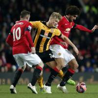 Squeezed out: Cambridge's Cameron McGeehan (center) is challenged by Manchester United's Marouane Fellaini (right) and Wayne Rooney on Tuesday. | REUTERS