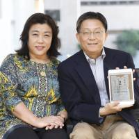 Peace and quiet: Jie Quan poses for a photo in Tokyo with her husband, Zhiqiang Jing, who is holding a Chinese calendar page of the day their son was born. | CHIEKO KATO