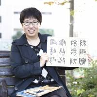 Yangyue Fan holds one of her calligraphy books in Tokyo. | CHIEKO KATO