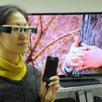 People who are deaf or blind can participate in a movie screening by wearing a special pair of UDCast glasses that are connected to an iPhone. | SATOKO KAWASAKI