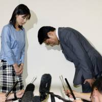 Liberal Democratic Party lawmaker Akihiro Suzuki apologizes to Ayaka Shiomura in June 2014 for a sexist remark. | KYODO