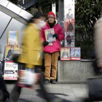 Struggling: A homeless man sells The Big Issue magazine on the streets of Tokyo. A book by economist Thomas Piketty titled 'Capital in the Twenty-First Century' has been drawing attention to income inequality.   BLOOMBERG
