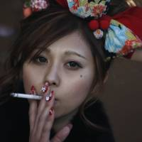 Small pleasures: A young woman takes a smoke break while celebrating Coming-of-Age Day at an amusement park last month.   REUTERS