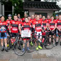 Red sweater day: The Knights in White Lycra are pictured before last year's long-distance charity ride from Tokyo to Minamisanriku. Robert Williams is fifth from left. |  IVAN DOHERTY