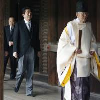 Prime Minister Shinzo Abe follows a Shinto priest to pay respect for the war dead at Yasukuni Shrine in Tokyo on Dec. 26, 2014.  | AP