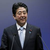 Prime Minister Shinzo Abe speaks during the party's annual convention in Tokyo on Sunday. The Robot Revolution Realization Committee, an advisory panel appointed by Abe, will review existing radio and civil aeronautics laws and set up industry-run best practices for drones. | BLOOMBERG