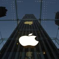 The Apple logo is illuminated in the entrance to the Fifth Avenue Apple store in New York in 2013. Apple's widely used iTunes and app stores suffered a rare breakdown Wednesday, frustrating millions of music lovers and mobile device owners around the world.   AP